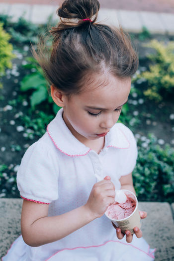 High angle view of cute girl holding ice cream while sitting outdoors
