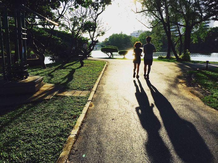 Rear view of siblings walking on footpath against trees