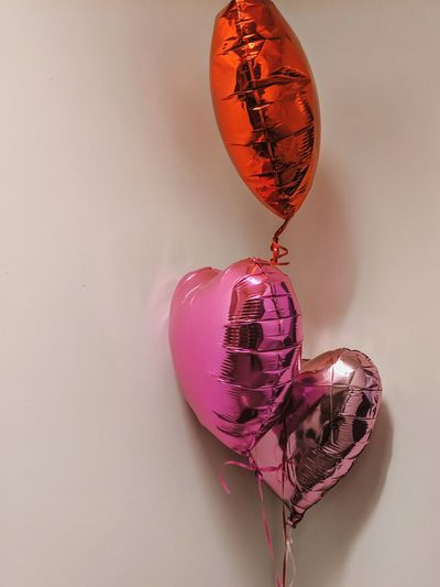 Close-up of heart shaped balloons against white background