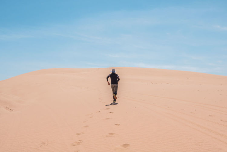 Man walking in desert against sky