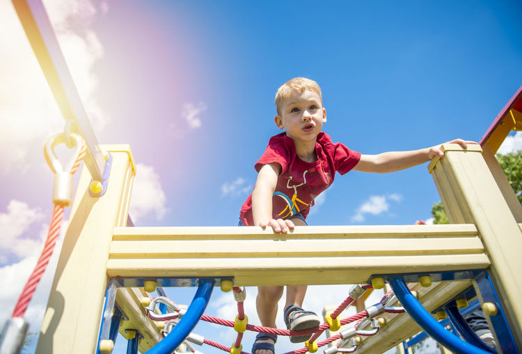 Low angle view of boy playing on jungle gym in playground