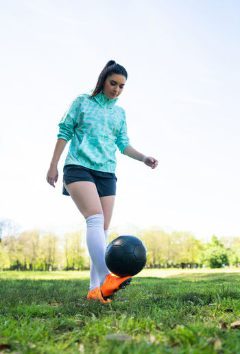 Full length of woman practicing with soccer ball against sky