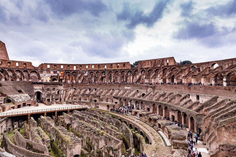 Colosseum against cloudy sky in city