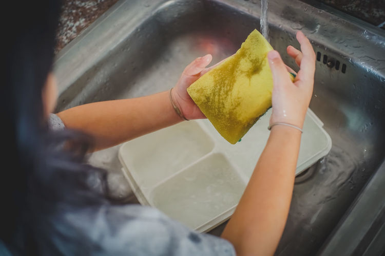 Kid washing dishes. Dishes Washing Washing Dishes Cleaning Food Food And Drink Freshness Girl Hand Holding Home Working Housework Human Body Part Human Hand Human Limb Hygiene Indoors  Kid Occupation One Person Preparation  Preparing Food Real People Sponge Washing Water Working Yellow Young Adult The Still Life Photographer - 2018 EyeEm Awards