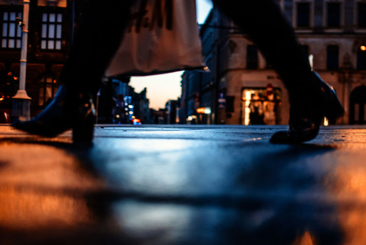 Low Section Of Woman Walking On Street At Night