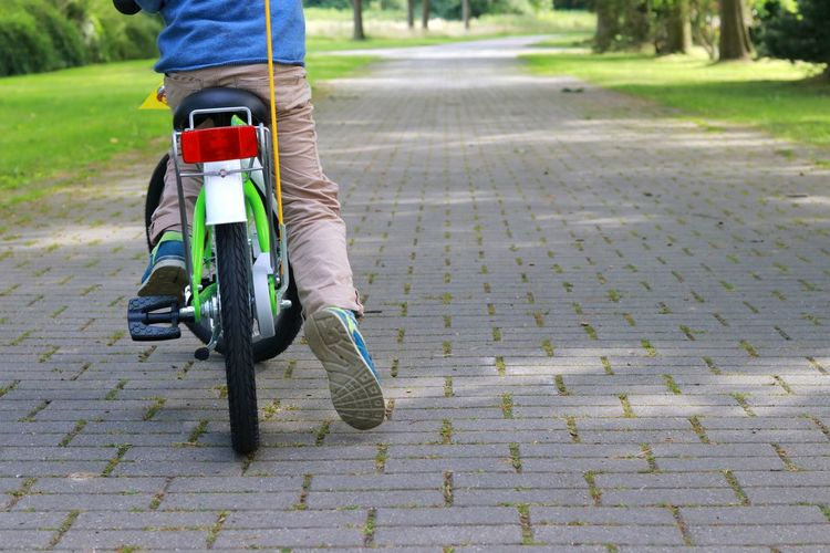 Low section of man riding bicycle on footpath