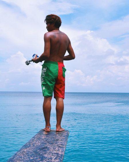 Rear View Of Shirtless Man Standing On Diving Platform