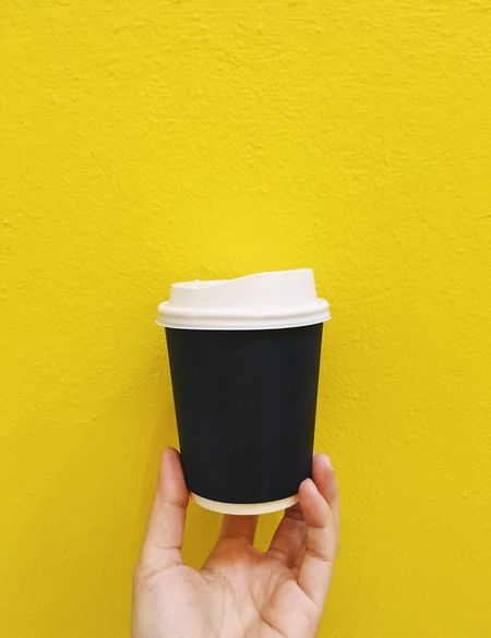 Human Hand Hand Holding Yellow Human Body Part One Person Wall - Building Feature Unrecognizable Person Body Part Personal Perspective Finger Human Finger Copy Space Lifestyles Cup Close-up Drink Indoors  Take Away Coffee Coffee Cup Coffee Break Paper Cup