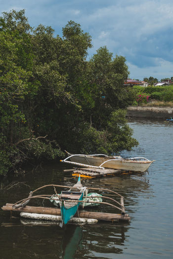 Boat moored in river against sky