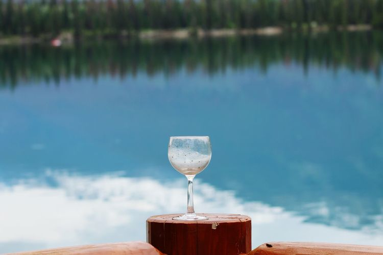 Close-up of drink on table against lake