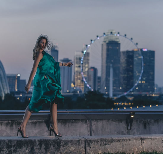 Full length of woman with cityscape in background