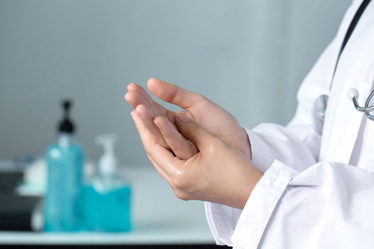 Midsection of doctor applying sanitizer on hands in office