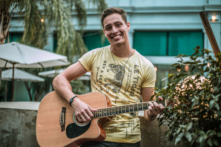 Portrait of young man playing guitar while standing against building