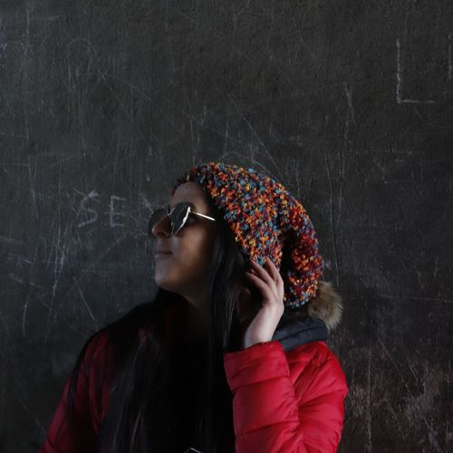 Woman wearing sunglasses while standing against blackboard