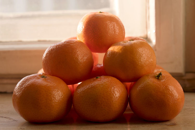 Ordered group of clementines, mandarins on a sunlit window sill - pyramid Citrus  EyeEmNewHere Lines Orange Pyramid Snack Sunlight Citrus Fruit Clementine Clementines Close-up Delicious Freshness Fruit Group Of Objects Healthy Eating Healthy Food Indoors  Mandarins Minimalism No People Orange Color Order Rows Of Things Window Sill