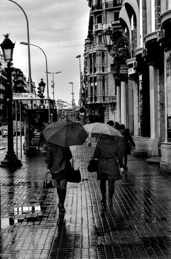 Woman walking on wet street during rainy season
