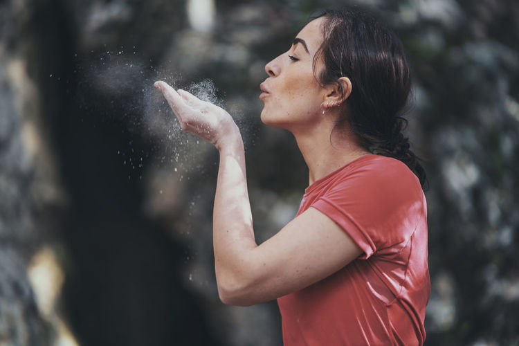Side view of young woman blowing sports chalk while standing outdoors