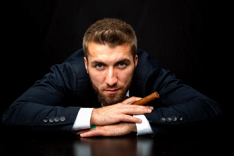 Attractive man with a cigar is relaxing on his desktop Businessman Relaxing Black Serious Tired Cigarette  Table Desktop Shooes Arrogant Attractive Career Luxury Lifestyles Handsome Office Sitting Men Males  People Adult Black Background One Person Indoors  Studio Shot