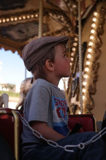 Cute boy sitting in carousel at amusement park