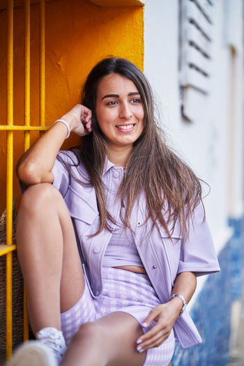 Portrait of a smiling young woman sitting outdoors