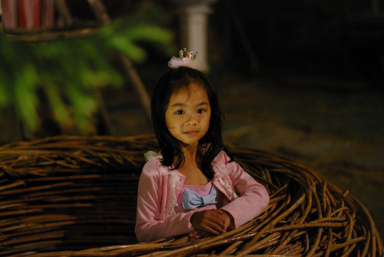 Portrait of cute girl standing by wicker nest
