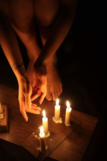 Close-Up Of Woman Bending By Candles On Table In Darkroom