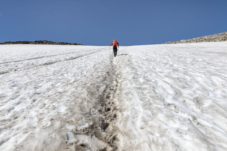 Hiker walking up a steep snowfield on the way up to Scandinavia's highest mountain on a sunny summer day Nature Day Outdoors Sunny Knickowski Jotunheimen 2018 Challenge Extreme Terrain One Person Full Length Leisure Activity Sky Lifestyles Snow Scenics - Nature Trip Vacations Clear Sky Cold Temperature Real People Holiday Rear View Walking Rear View Below Summer Galdhøpiggen Hiking Strength Track - Imprint Rock Formation Moving Up Steep Looking Up Effort Toughness The Way Forward Clear Sky White Color Mountain High Up Low Angle View Men Footpath Backpack SnowField Non-urban Scene Landscape