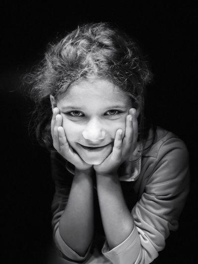 Portrait of smiling girl against black background