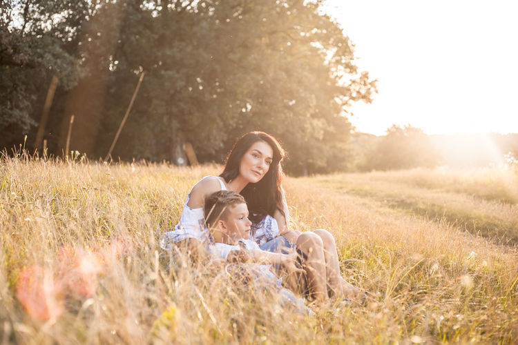 Mother and Son This Is Natural Beauty Sunlight Young Adult Grass Nature Happiness Plant Adult Emotion Women Relaxation Land Leisure Activity Smiling Field Lens Flare Hair People Sitting One Animal Hairstyle Outdoors Positive Emotion