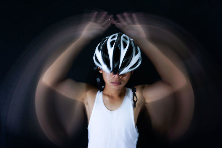 Close-up of man with blurred hands wearing bicycle helmet against black background