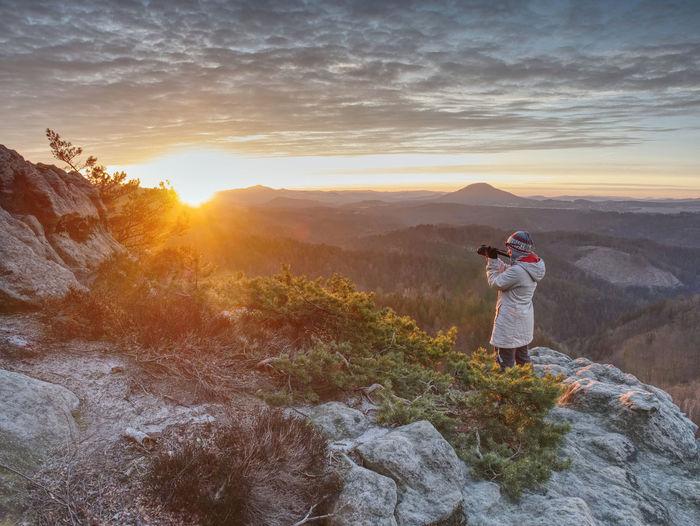 Woman photographer works at camera on fiber glass tripod. misty spring daybreak above misty valley