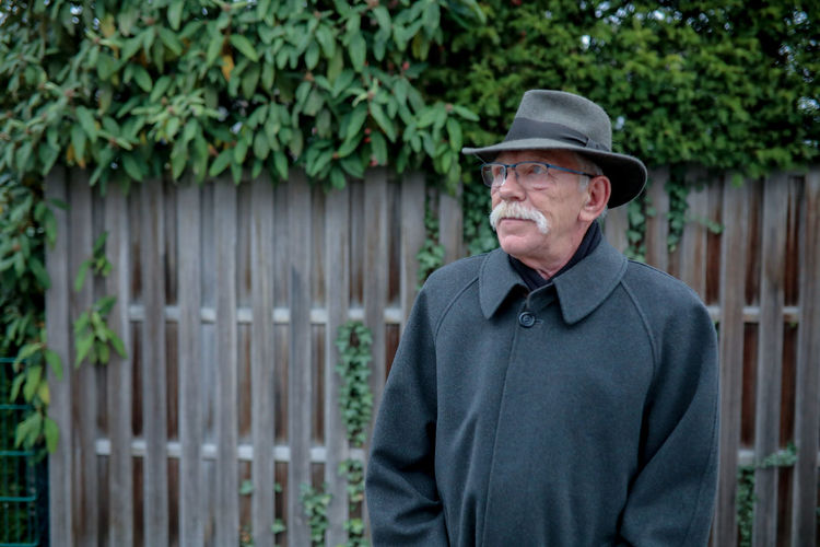 Portrait of man wearing hat standing against fence