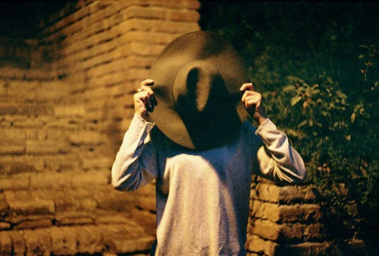 Person covering face with hat while standing outdoors