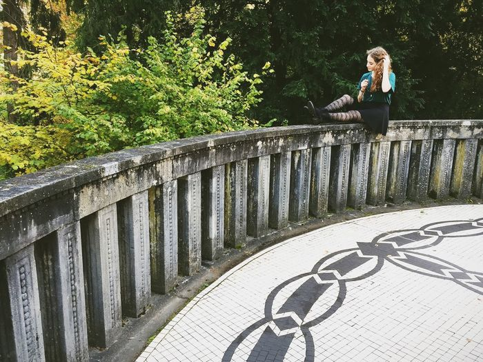 Young woman sitting on concrete railing at park