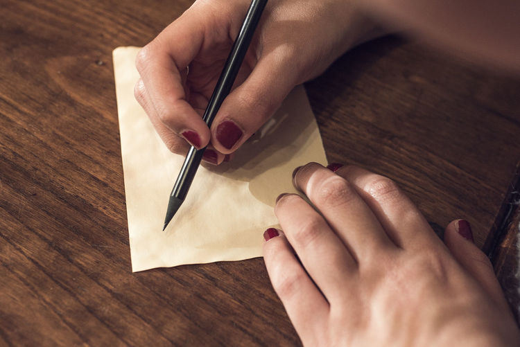 Close-Up Of Woman Writing On Paper At Table