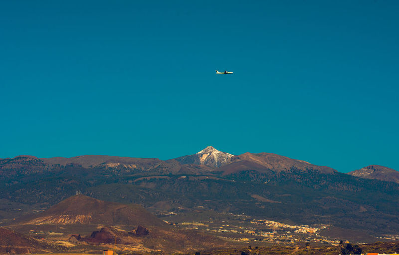 Airplane flying over mountains against clear blue sky