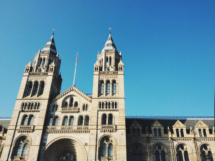 Low angle view of natural history museum against clear blue sky in city