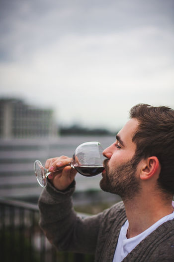 Young Man drinking red Wine on a Rooftop Red Wine Rooftop Drink Focus On Foreground Glass Headshot Holding Lifestyles Men One Person Outdoors Portrait Profile View Real People Refreshment Wine Wineglass Young Adult Young Men