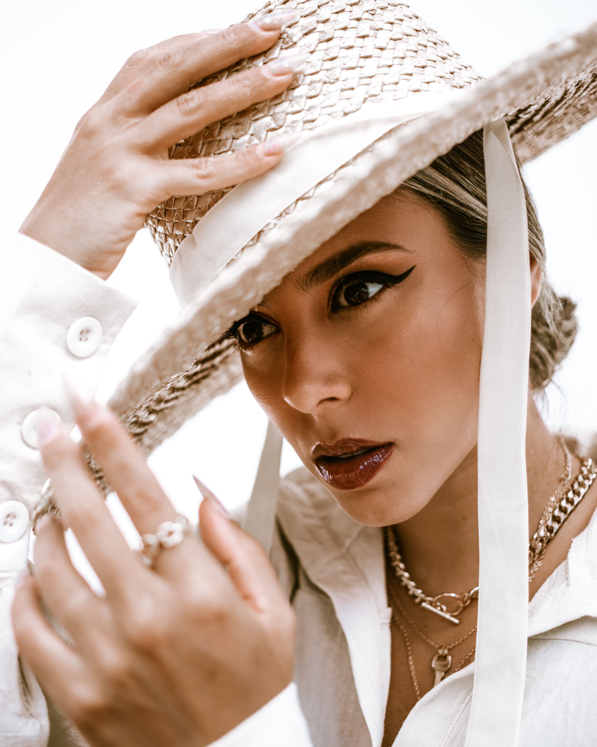 adult, portrait, one person, women, clothing, hat, young adult, headshot, fashion accessory, jewelry, female, fashion, sun hat, studio shot, person, human face, looking, traditional clothing, headgear, hand, looking at camera, white, elegance, holding, bride, veil, close-up, emotion, indoors