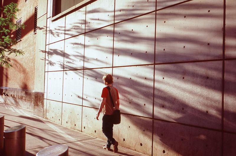 Pedestrian walking in front of wall