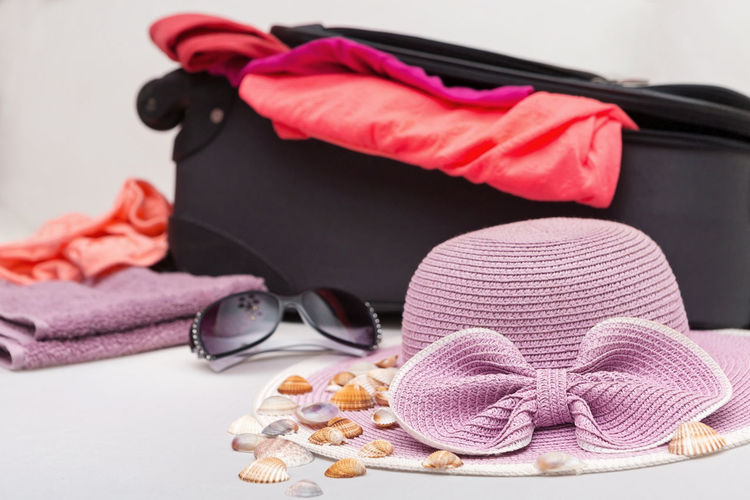Close-up of sunglasses with seashells and hat on table