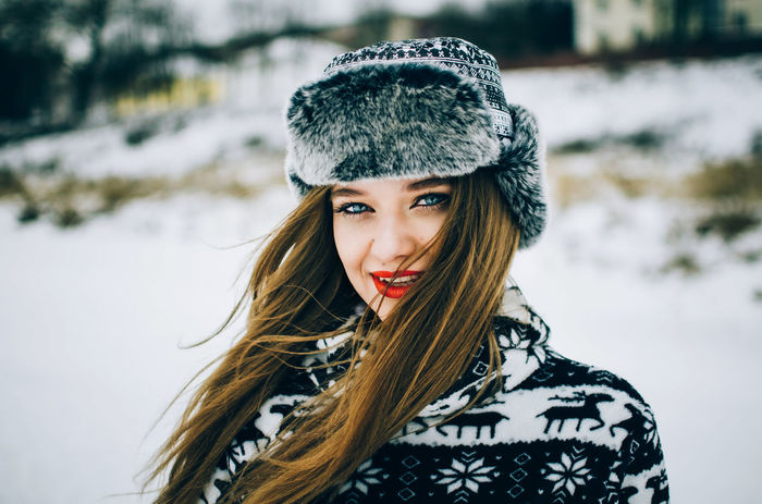 Portrait of handsome young woman with blue eyes looking camera and wearing warm hat in winter. Beautiful Woman Clothing Cold Temperature Hair Hairstyle Headshot Long Hair Looking At Camera One Person Outdoors Portrait Real People Snow Warm Clothing Winter Young Adult