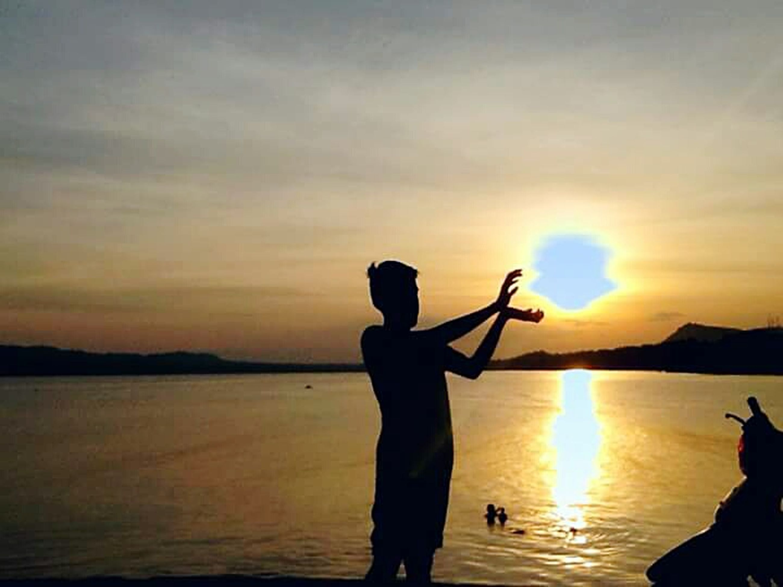 sunset, water, lifestyles, leisure activity, silhouette, sun, sky, sea, men, holding, standing, beauty in nature, scenics, nature, reflection, rear view, orange color, tranquil scene