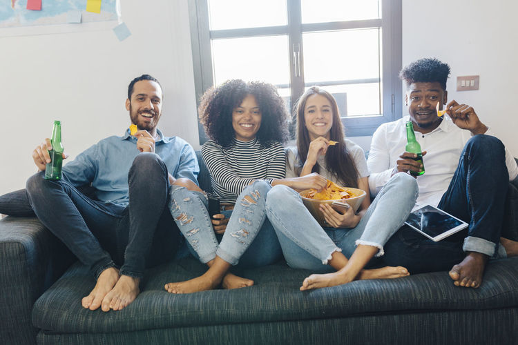 Friends sitting on sofa at home