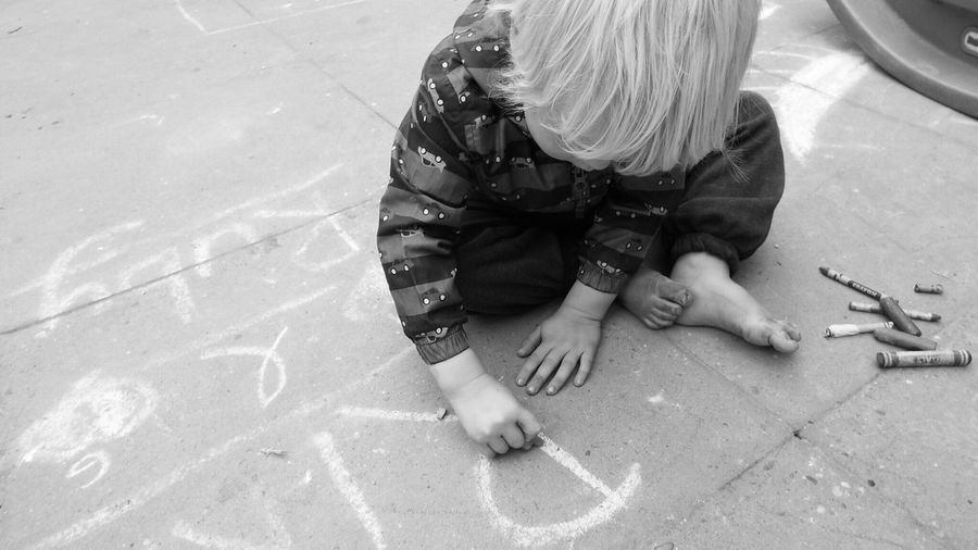 High angle view of boy writing text on street