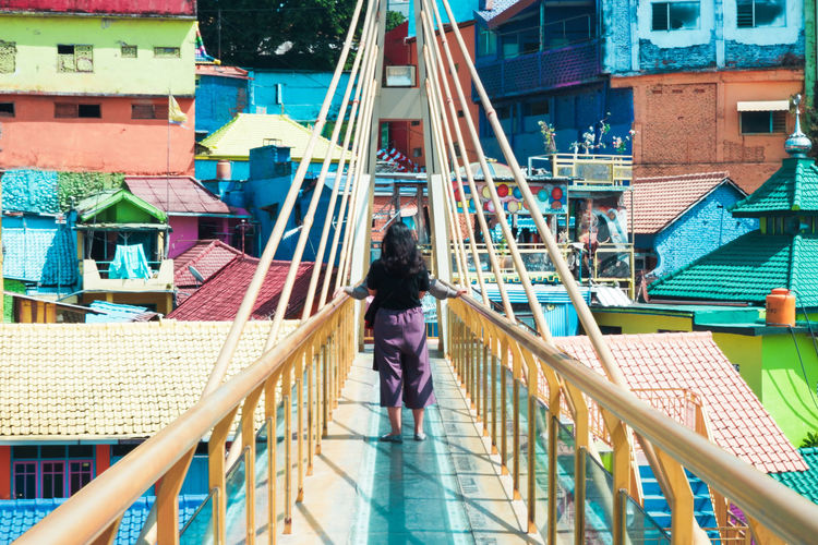 Rear view of woman standing on railing against buildings in city
