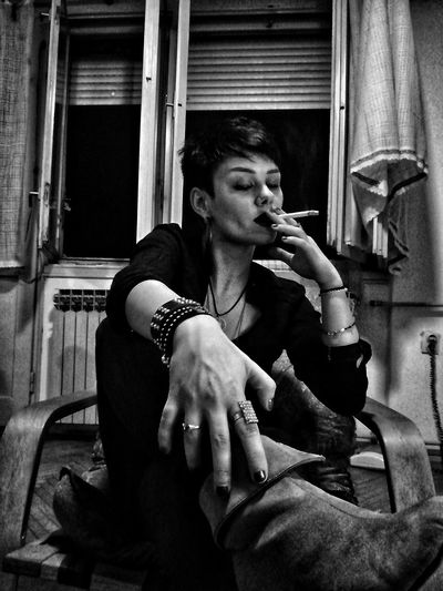 Mid adult woman holding cigarette at home