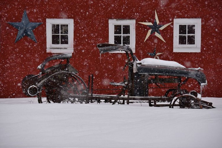 Eclectic vehicle against red barn in winter Americana Architecture Barn Building Exterior Cold Temperature Eclectic Frozen Junk No People Outdoors Patriotic Red Residential Building Rustic Snow Snowflake Snowing Stars Vintage Car White Color Window Winter