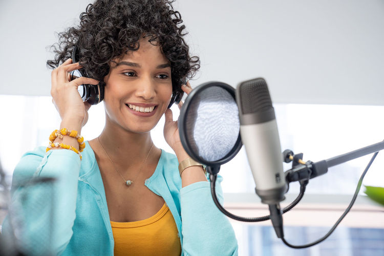 Smiling woman wearing headphones in radio studio