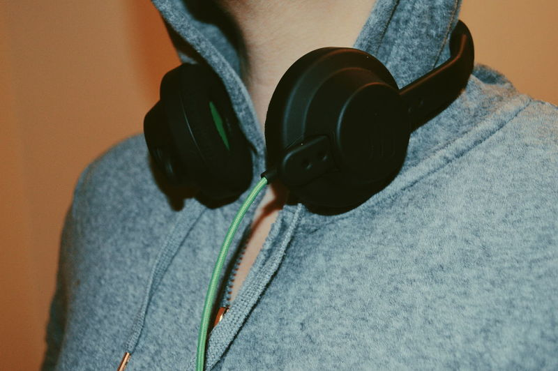 Midsection of man wearing headphones against brown background